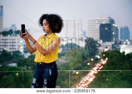 Young woman taking a photo in the cityscape