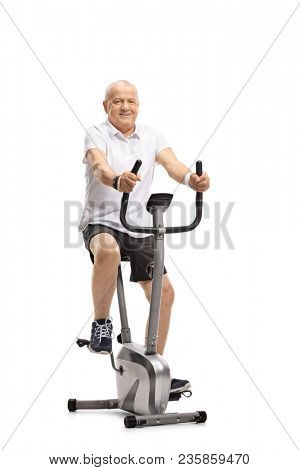 Mature man working out on a stationary bike isolated on white background