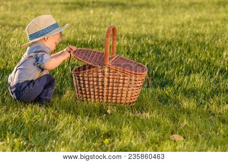 Portrait of toddler child outdoors. Rural scene with one year old baby boy wearing straw hat looking in picnic basket