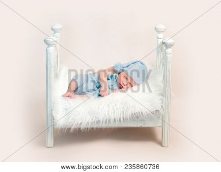 Newborn boy in blue outfit sleeping on crib