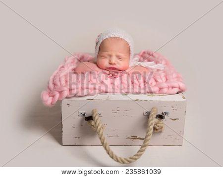 Sleeping newborn baby with chubby cheeks lying in box on rug