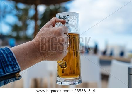 Hand Of Woman Holding A Pint Of Cold Beer Against Blurred Summer Background