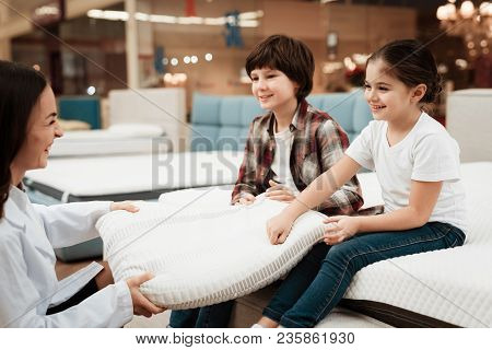 Beautiful Woman Dressed In White Robe Shows Orthopedic Pillow To Young Children Sitting On Mattress.