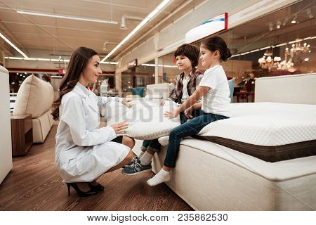 Attractive Woman Dressed In White Robe Shows Orthopedic Pillow To Young Children Sitting On Mattress