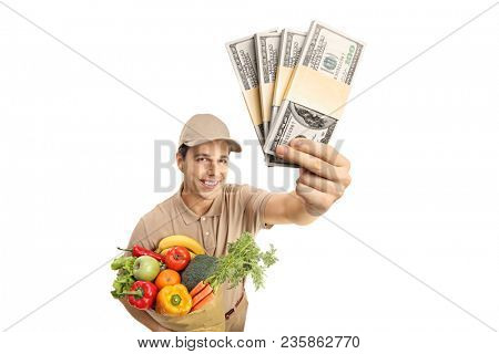 Delivery man holding a bag of groceries and bundles of money isolated on white background