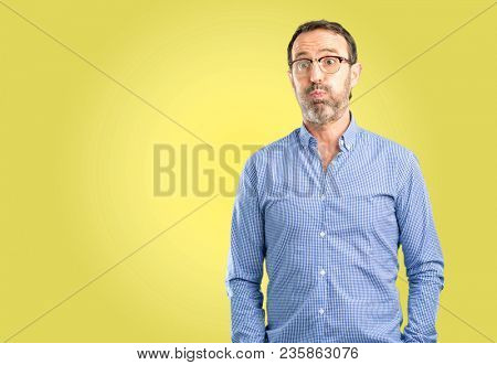 Handsome middle age man puffing out cheeks, having fun making funny face