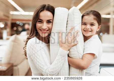 Smiling Little Girl With Beautiful Mother Hugs Pillows In Store Of Orthopedic Mattresses. Testing So