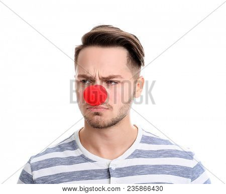 Young man with red clown nose on white background. April fool's day celebration