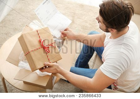 Young man unpacking parcel at home
