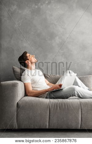 Pleased man 30s in basic clothing using laptop while lying on comfortable sofa in gray apartment