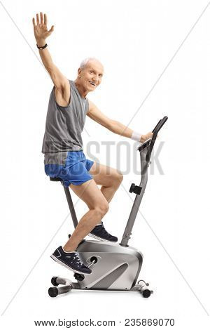Elderly man exercising on a stationary bike and waving at the camera isolated on white background poster