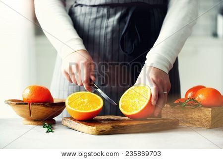 Woman Hands Slicing Orange, Cutting Citrus Fruit. Knife, Wooden Cutting Board On Design White Kitche