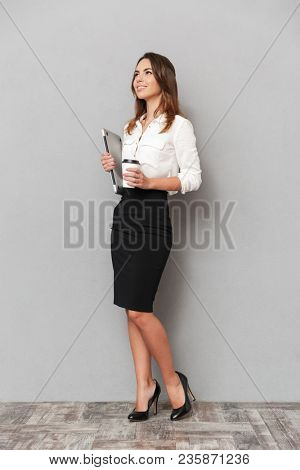 Full length portrait of a confident young business woman holding laptop computer and cup of coffee to go isolated over white background