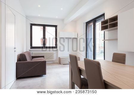 Modern apartment living room with bright windows. Nobody inside