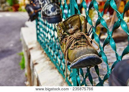 Old battered boot with lace rope used as decoration for shabby metal fence.