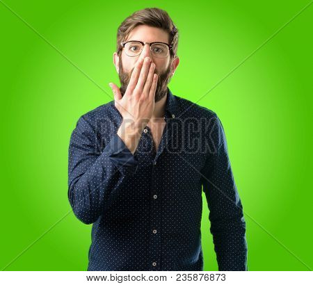 Young hipster man with big beard covers mouth in shock, looks shy, expressing silence and mistake concepts, scared over green background