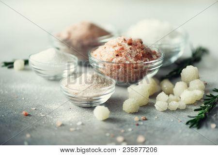 Mix Of Different Salt Types On Grey Concrete Background. Sea Salts, Black And Pink Himalayan Salt Cr