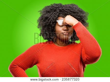 Beautiful african woman with sleepy expression, being overworked and tired, rubbes nose because of weariness