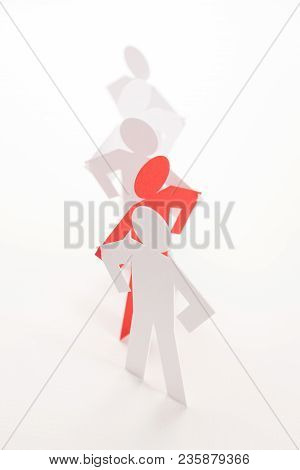 Linked Line Of Five  Paper Standing Figure With Red One On Bright White Background. In Concept Of Co