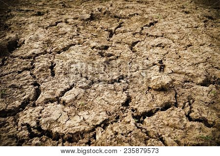Cracked Earth , Hot And Dry Empty Land. Clay Soil To Crack Texture .drought Land Against A Sun With