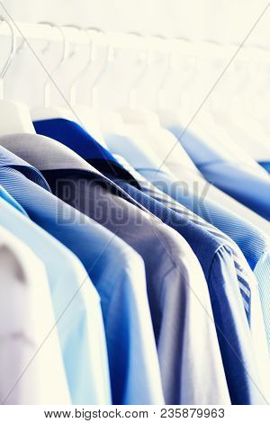 Blue Color Clothes. Male Clothes, Jackets And Shirts Hanging On Clothes Rail. Copy Space. Banner.