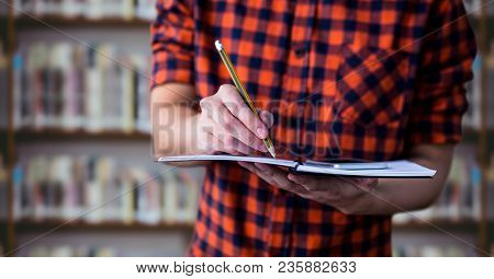 College student mid section with notebook against blurry bookshelf