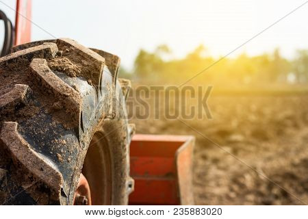 Tractor Tire On Field. Agriculture Tractor Plowing Field.