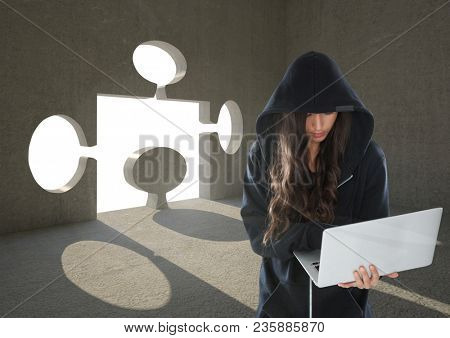 Woman hacker working on laptop in front of background with a puzzle hole