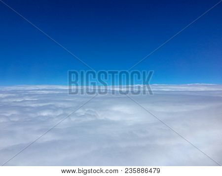 Pilot View From Aircraft Cockpit In Blue Sky Over White Cloud Ceiling In Stratosphere