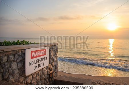 Warning Sign Board 'no Lifeguard On Duty' On Rock Wall At Beach In Sunrise And Copy Space