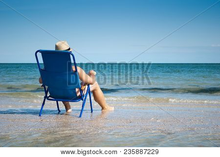 Young Man Sitting On A Deckchair On The Sea Shore Ocean Resting Sunbathing Looking At The Sea Beach