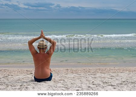 Young Man In A Straw Hat Sits On The Seashore From The Back, Summer Beach Waves Sky With Clouds, San