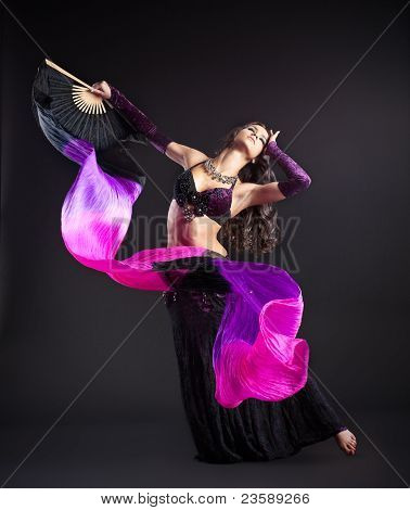 young beauty girl in arabic costume dance with fantail and purple veil in dark poster