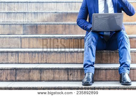 Businessman Sitting On Stairs And Using Laptop