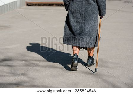 On A Sunny Day A Old Woman Walking Down The Street With Walking Stick. The Woman's Shadow Is Visible
