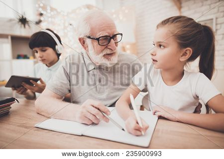 Grandfather, grandson and granddaughter at table at home. Grandpa is helping girl with homework. poster