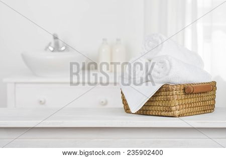 Towels Basket On Wooden Table Top With Blurred Bathroom Interior