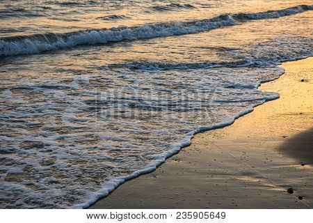 Waves Approaching Sandy Beach During Sunset