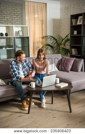 Front View Of Smiling Couple On Couch Using Laptop In Cozy Living Room