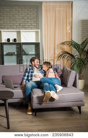 Young Couple Lying On Couch In Modern Living Room