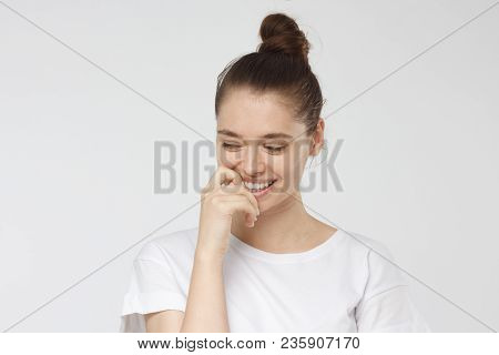 Naturally Beautiful Young Woman Isolated On Gray Background With Eyes Looking Down, Being Shy, Touch