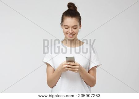 Indoor Shot Of Good-looking Young Woman Isolated On Gray Background Looking At Smartphone, Smiling O