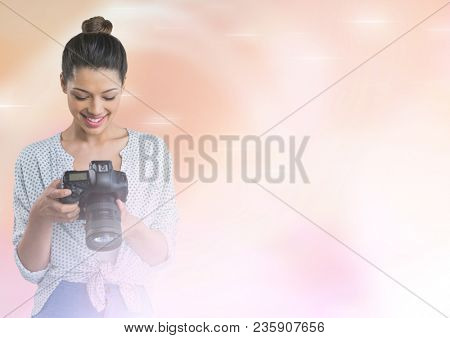 Smiling photographer looking at her camera in fog