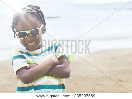 Boy in sunglasses arms folded against blurry beach with flare