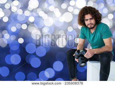 photographer with camera on the hands, sitting. Blue bokeh background