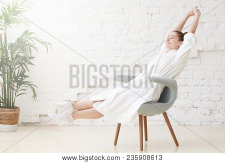 Horizontal Shot Of Young Smiling Woman In White Bathrobe Stretching In The Morning After Waking Up