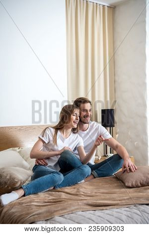 Young Smiling Woman With Boyfriend In Bedroom With Modern Design