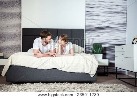 Happy Couple Lying And Talking In Cozy Modern Bedroom