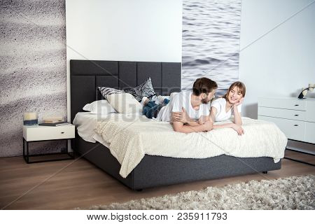 Smiling Young Couple Lying In Bedroom With Design Interior