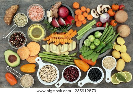Healthy eating food with vegetables, fruit, grains, pulses, herbs, spice, olive oil and himalayan salt on marble background. Super foods high in antioxidants, vitamins, minerals and anthocyanins.